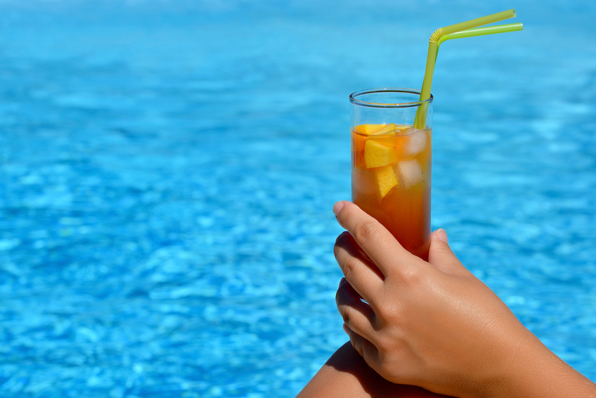 Real female beauty enjoying her summer vacation at swimming pool drinking cocktail